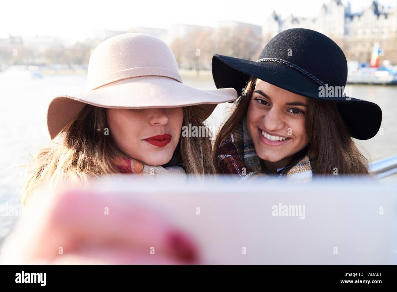 UK, London, two women wearing floppy hats taking a selfie on Millennium Bridge Stock Photo