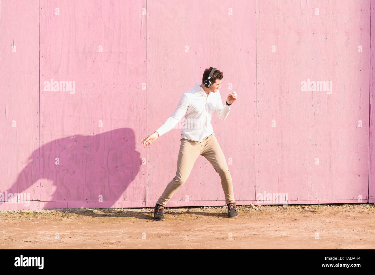 Exuberant young man listening to music in front of pink wall - Stock Image