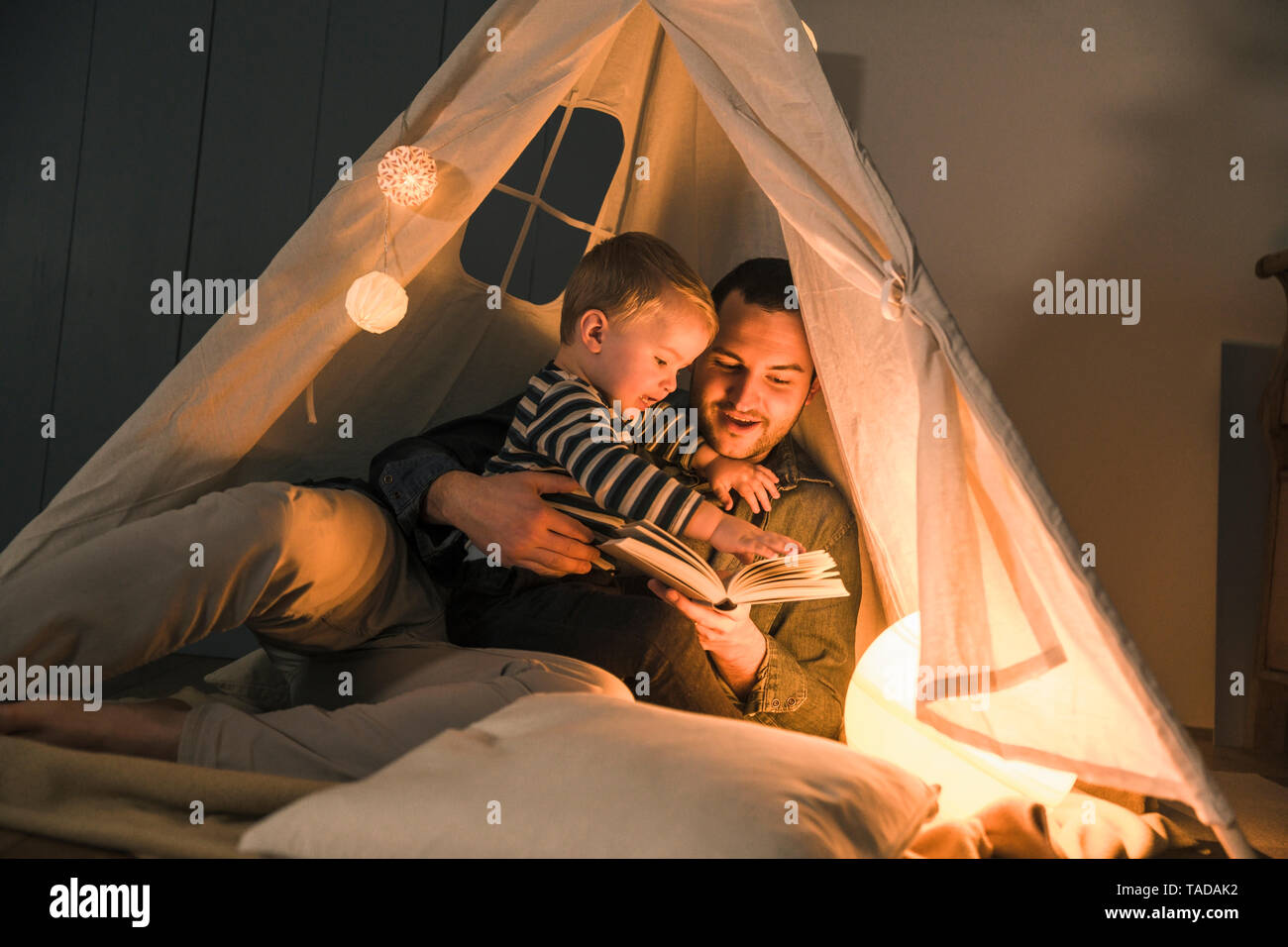 Father reading book to son at an illuminated tent at home - Stock Image