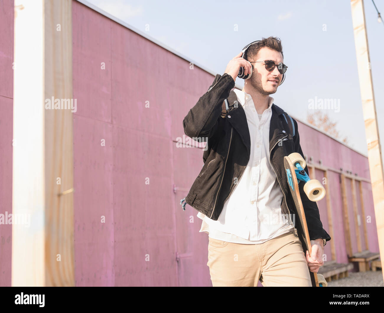 Young man with skatebaord and headphones on the move in the city - Stock Image