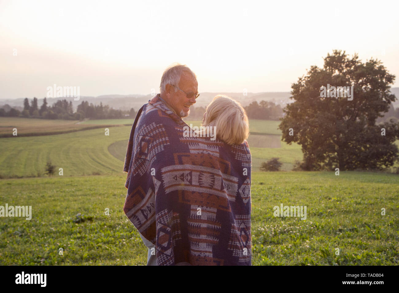 Happy senior couple standing on a meadow at sunset sharing blanket - Stock Image