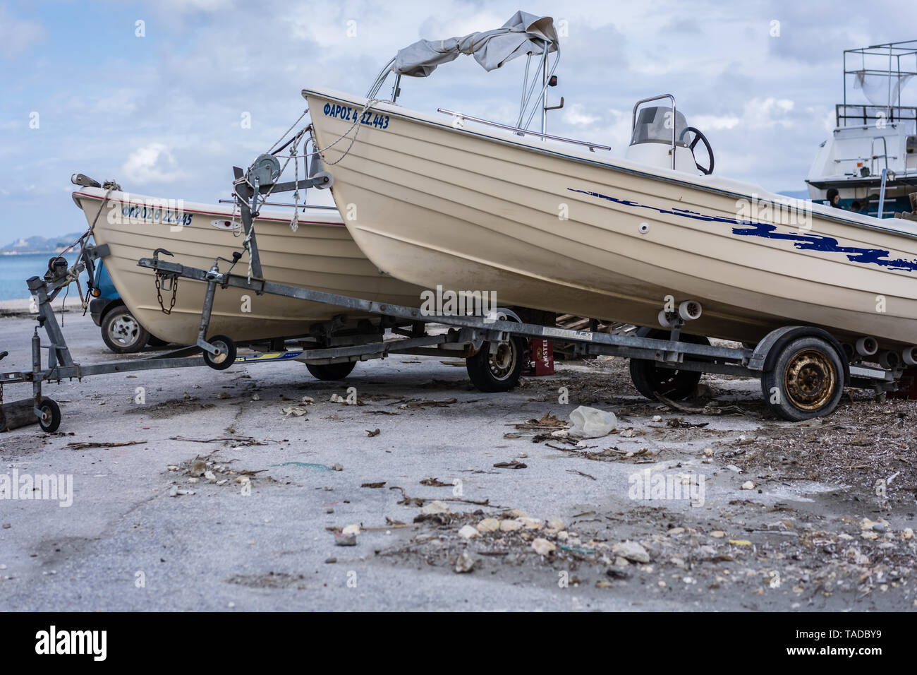 Zakynthos, Greece -  April 2019 : Fisherman boats on car trailers prepared for work in the port and harbour in the Alykes Bay in Zante - Stock Image