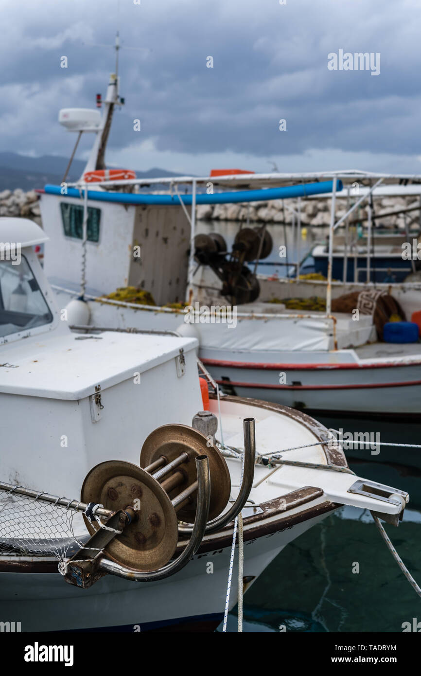 Zakynthos, Greece -  April 2019 : Fisherman boats in the port and harbour in the Alykes Bay in Zante, with stormy dramatic clouds accumulating in the  - Stock Image