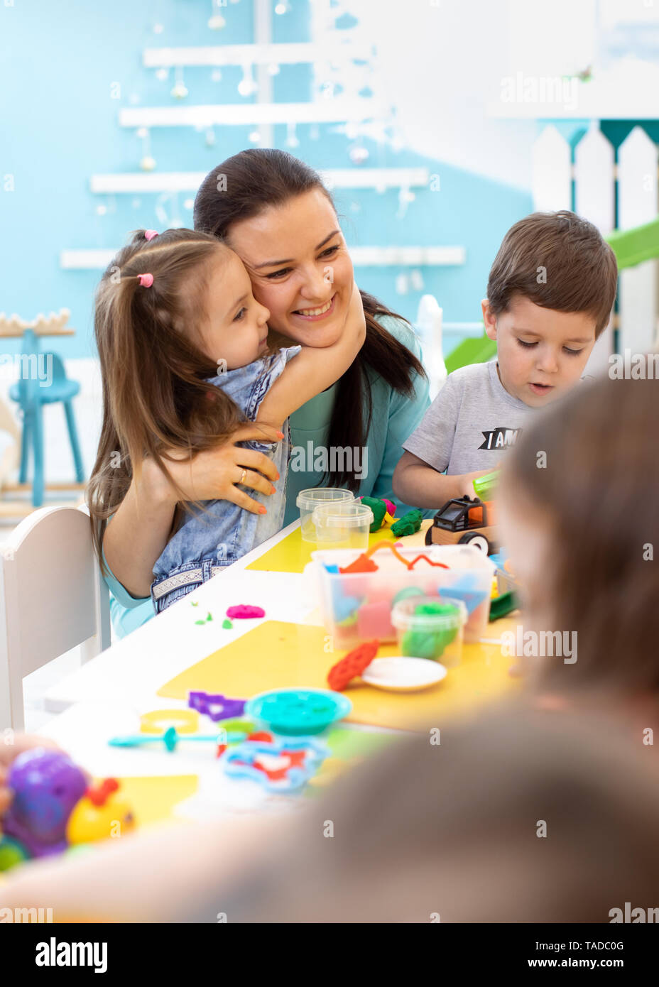 Teacher with group of kids working with plasticine at kindergarten or playschool - Stock Image