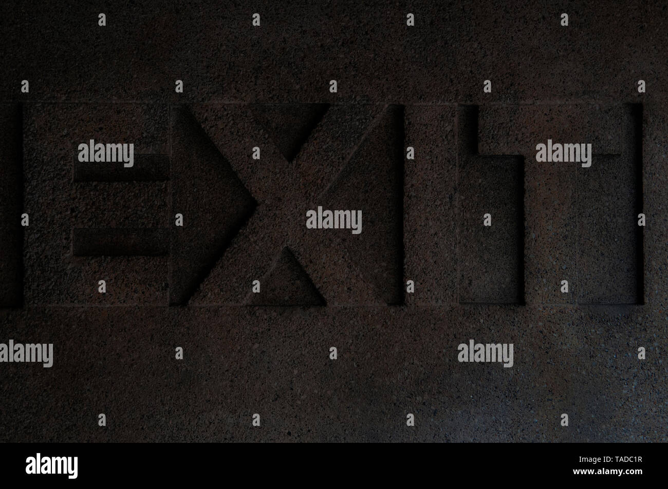 The Word Exit In Capital Letters Carved Into Stone - Stock Image