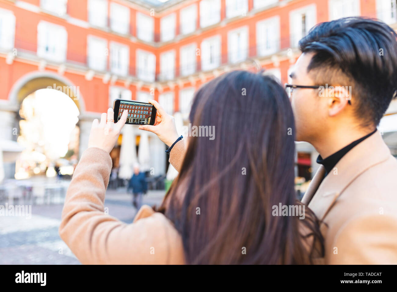 Spain, Madrid, young couple taking a smartphone picture in the city - Stock Image