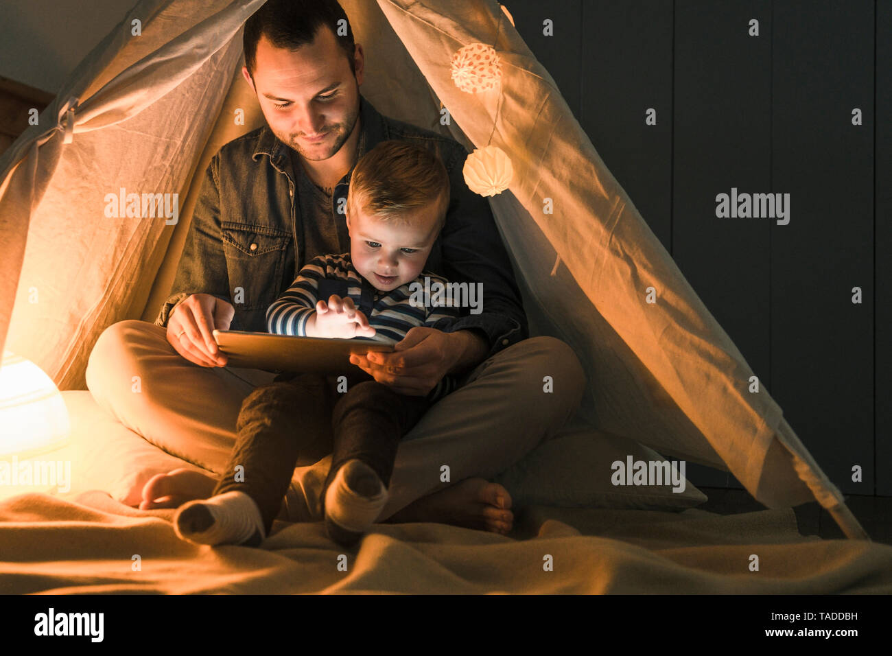 Father and son sharing a tablet in a dark tent at home - Stock Image