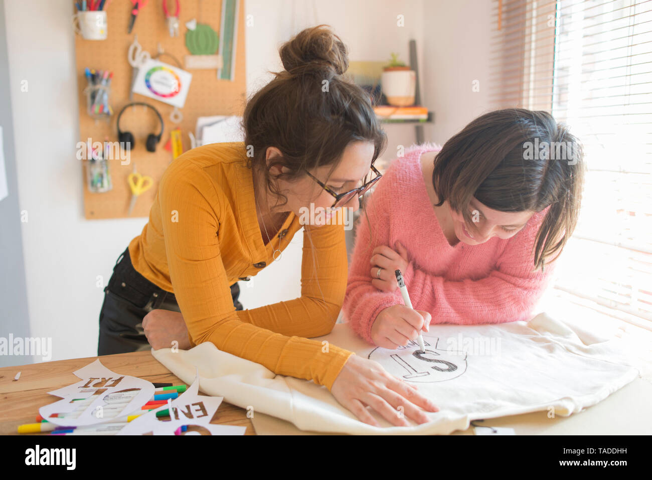 Two women drawing stencils for printing sweatshirts - Stock Image