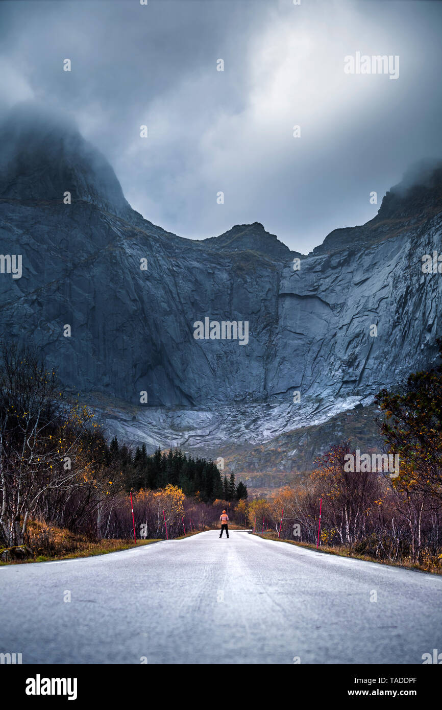 Norway, Lofoten Islands, man standing on empty road surrounded by rock face - Stock Image