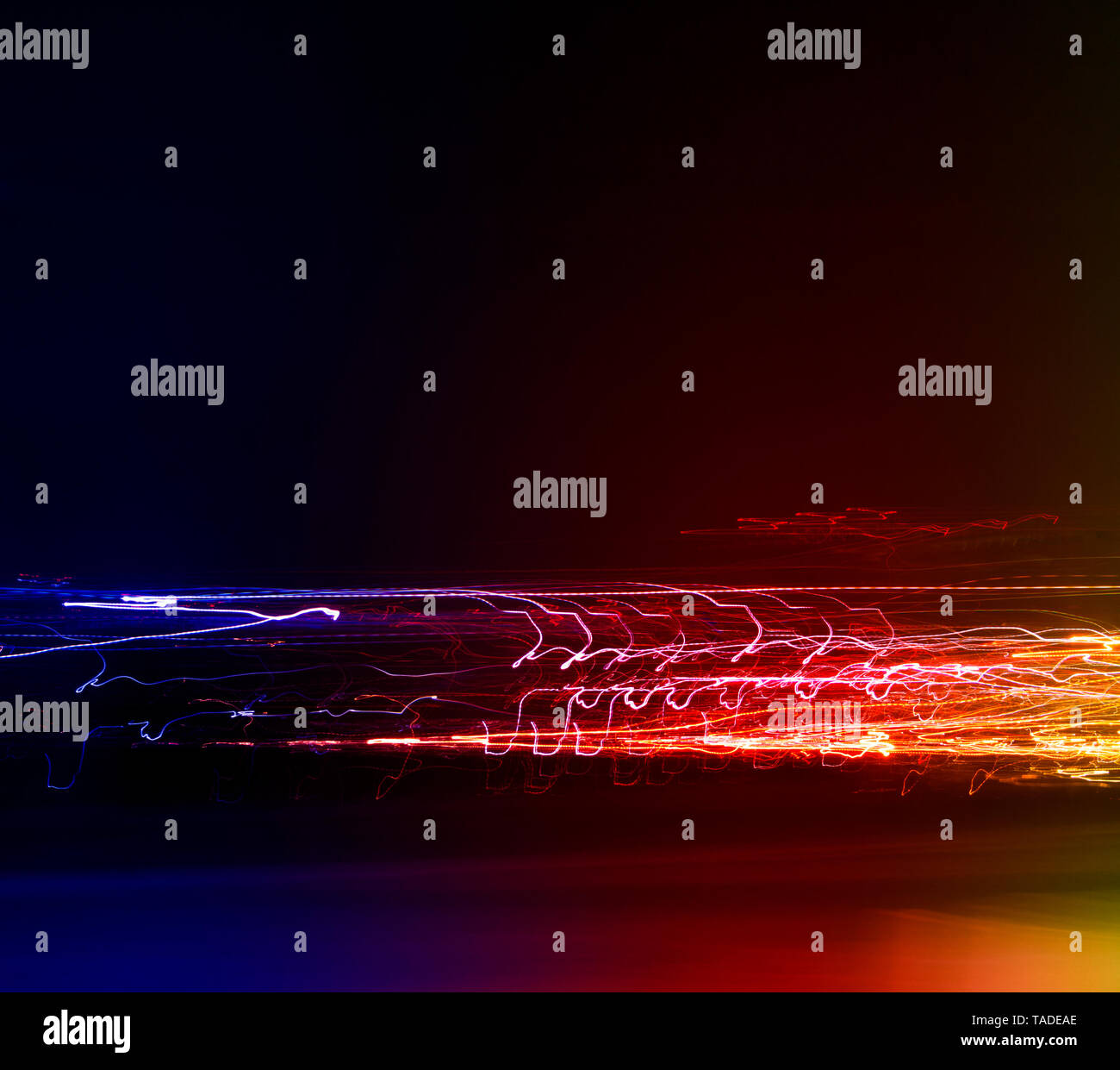 Different light trails of multicolored street lanterns and passing cars scattering in the dark, long exposure urban abstract background Stock Photo