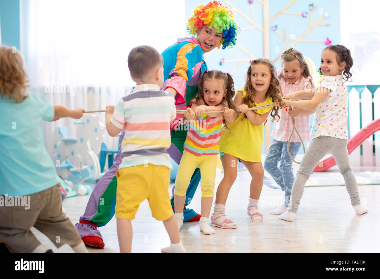 Excited kids and clown playing tug of war in club - Stock Image