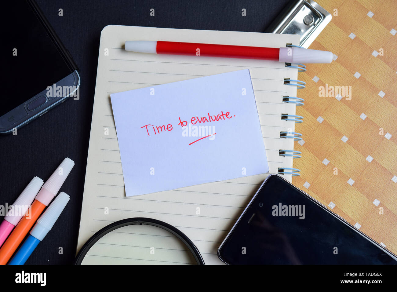 Time to Evaluate written on paper isolated on black table Stock Photo