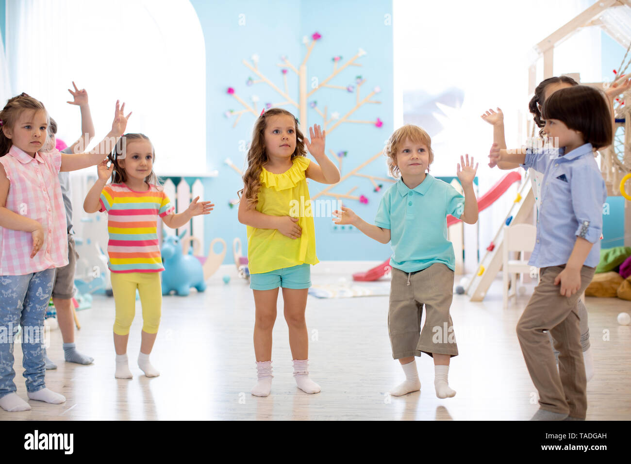 Happy children having fun dancing indoors in a sunny room at day care or entertainment center - Stock Image