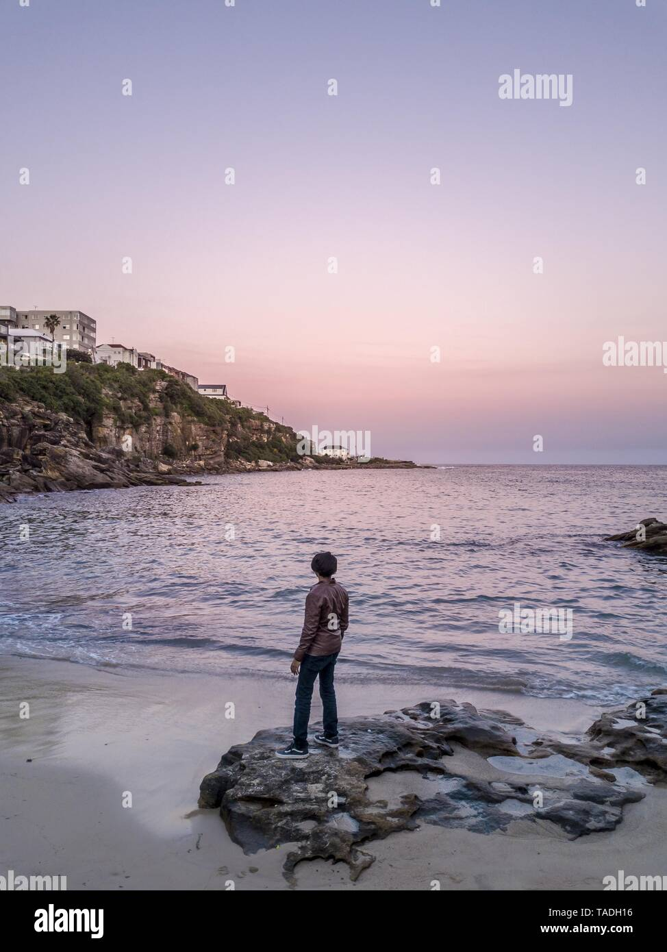 A male model in a coat standing on rocks at the shore of the sea enjoying the beautiful sunset Stock Photo
