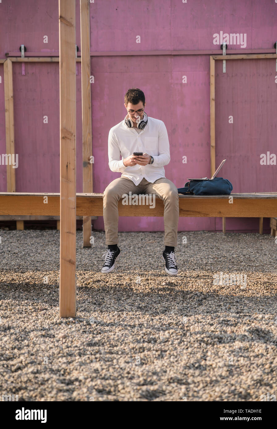 Young man sitting on platform using cell phone - Stock Image