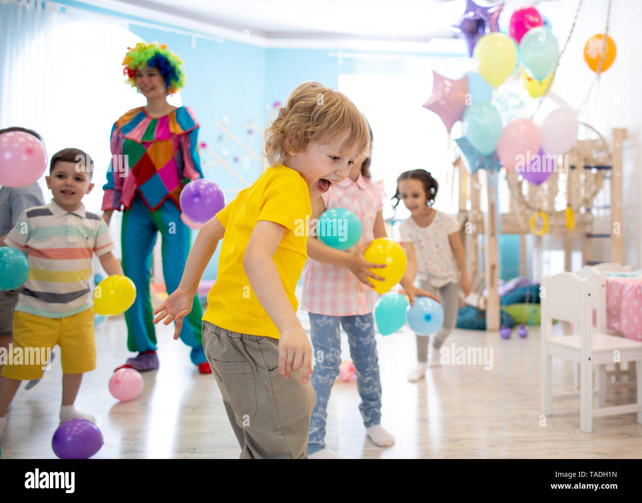 Group of children celebrate birthday party fun together - Stock Image
