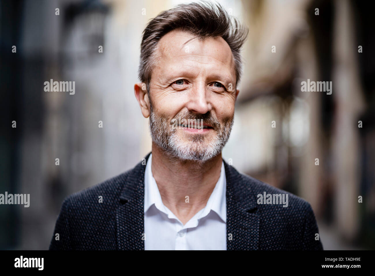 Portrait of smiling mature businessman with greying beard - Stock Image