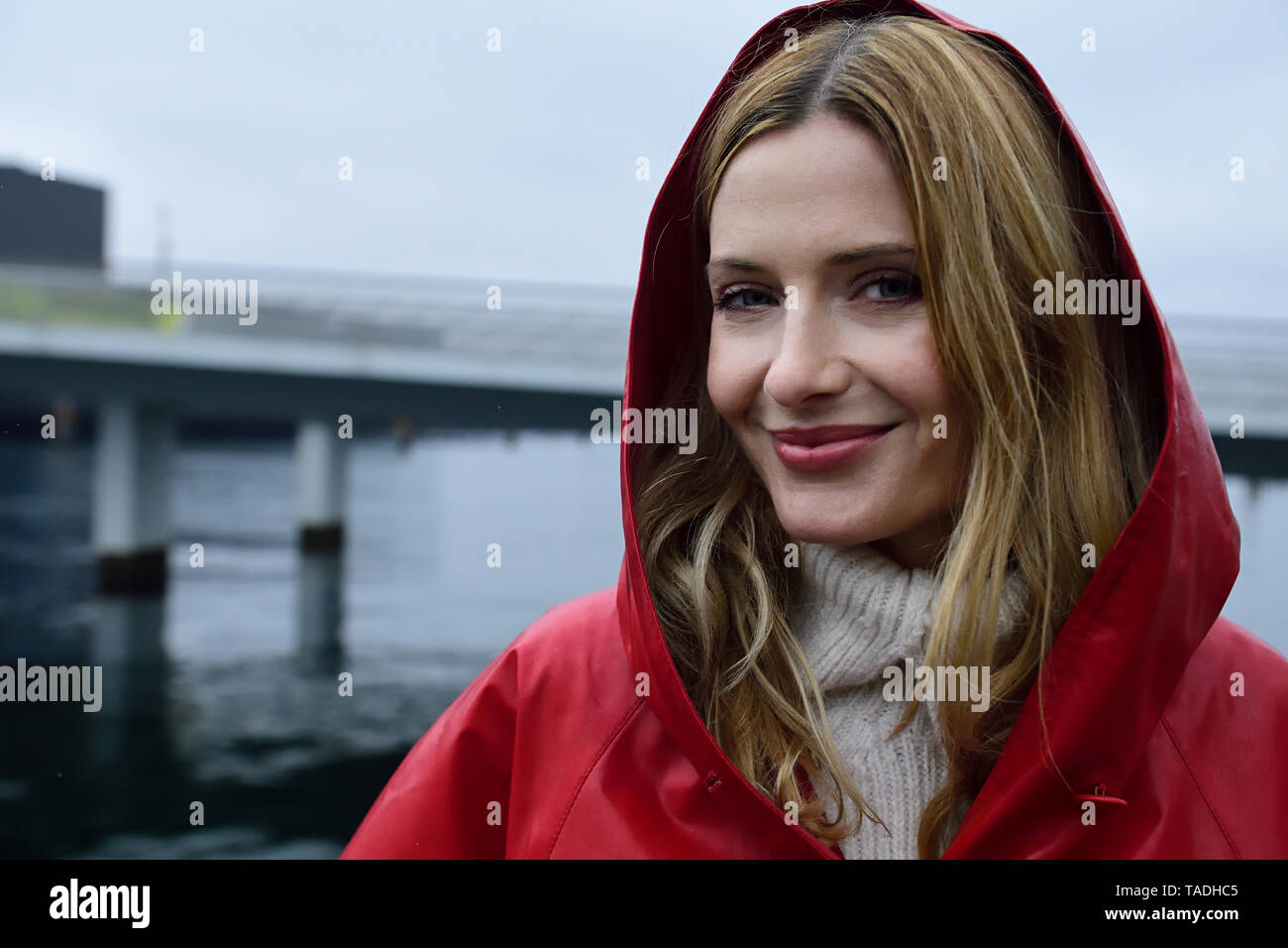 Denmark, Copenhagen, portrait of smiling woman at the waterfront in rainy weather - Stock Image