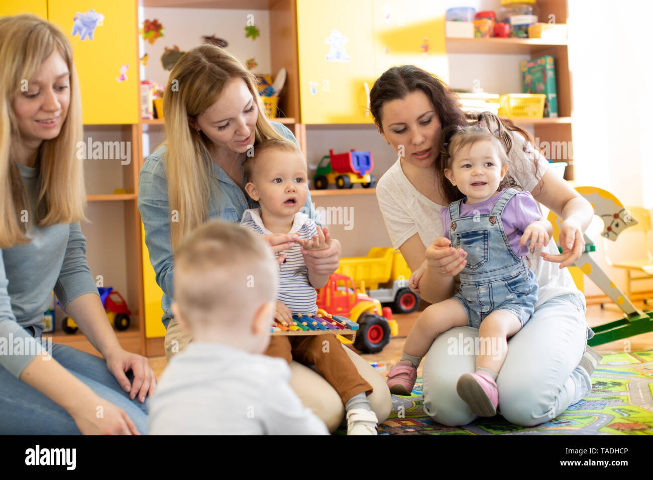 Babies with their mothers playing with toys in nursery - Stock Image