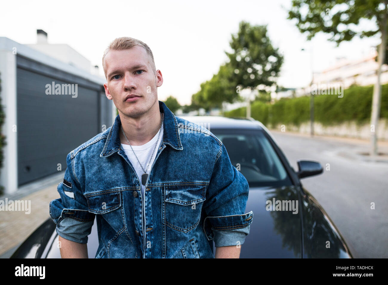 Portrait of young man in denim jacket standing in front of car - Stock Image