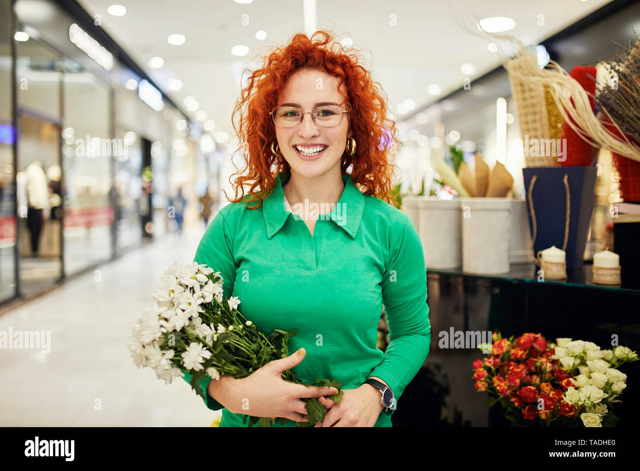 Portrait of smiling florist holding bunch of flowers in flower shop - Stock Image