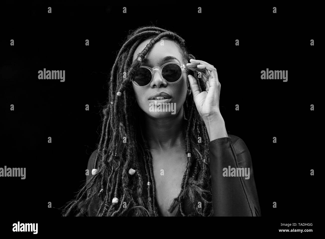 Portrait of woman with dreadlocks wearing sunglasses in front of black background - Stock Image