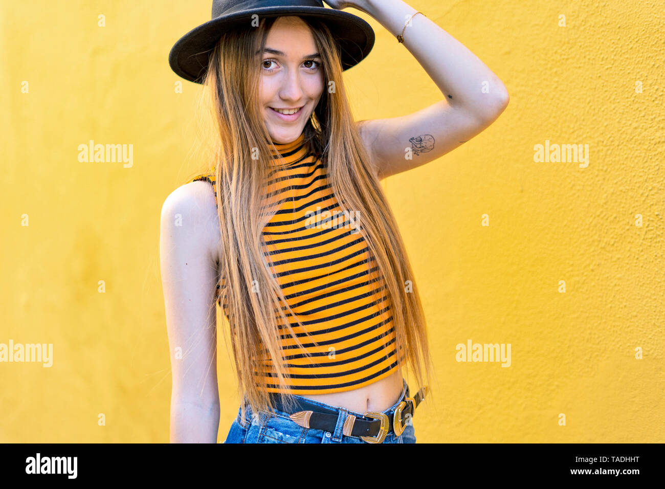 Portrait of smiling teenage girl wearing hat at yellow wall - Stock Image