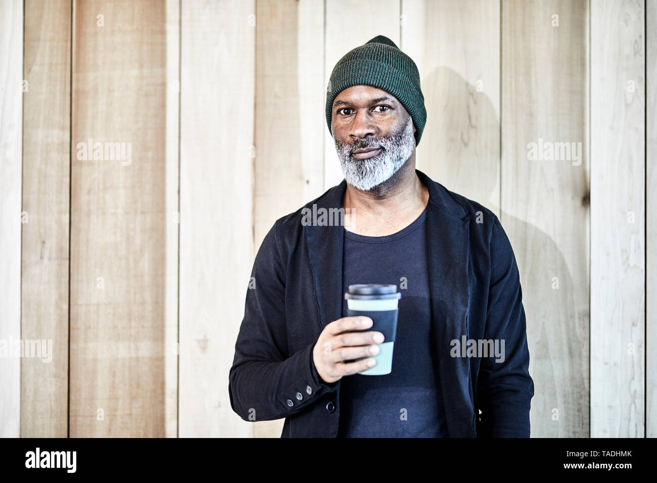 Portrait of confident mature businessman with takeaway coffee at wooden wall - Stock Image