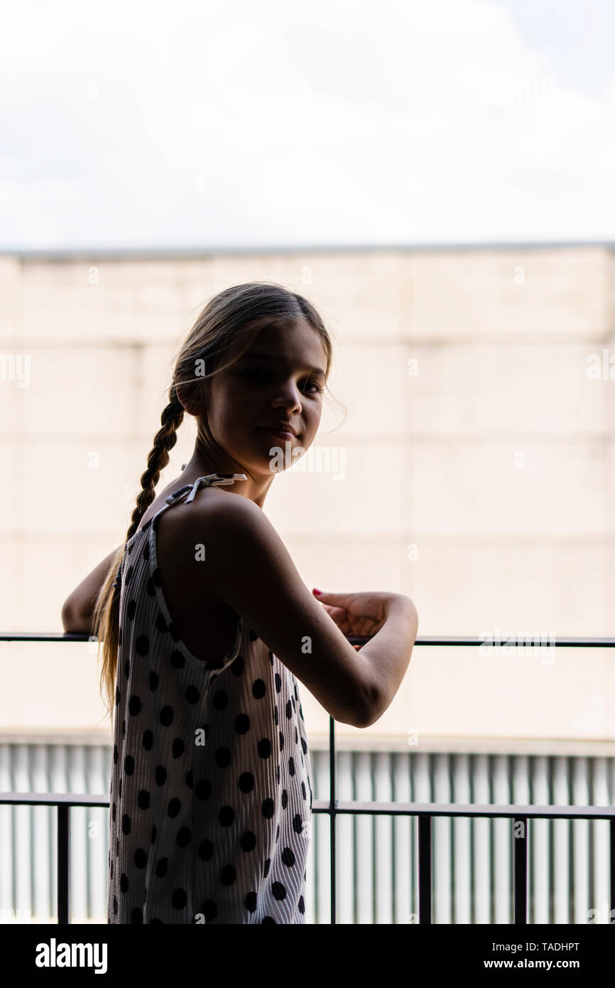 Girl wearing dotted dress standing on balcony - Stock Image