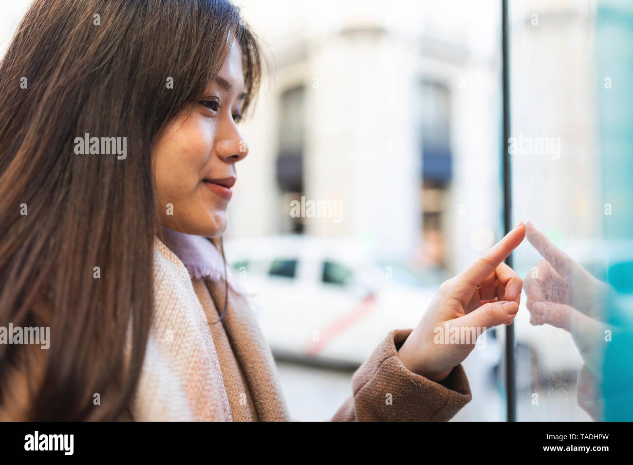 Spain, Madrid, young woman looking at the map and exploring the city - Stock Image