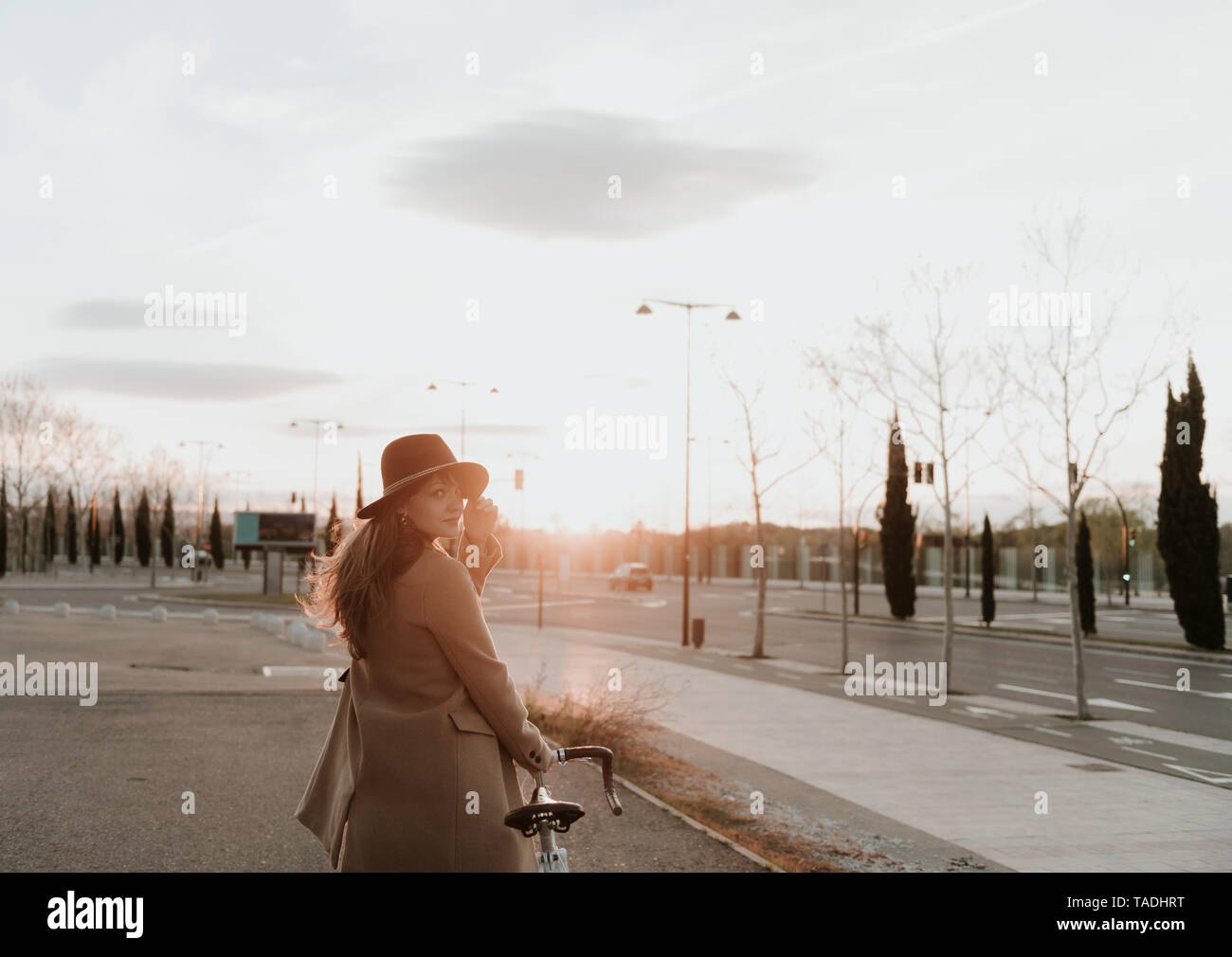 Young hipster woman going with a bicycle during sunset - Stock Image