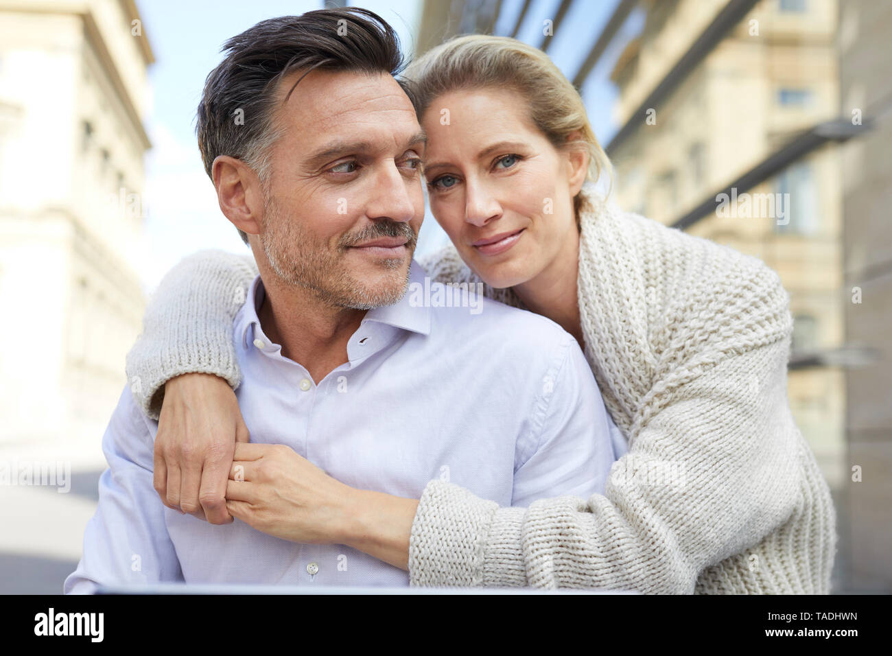 Portrait of smiling affectionate couple embracing outdoors - Stock Image
