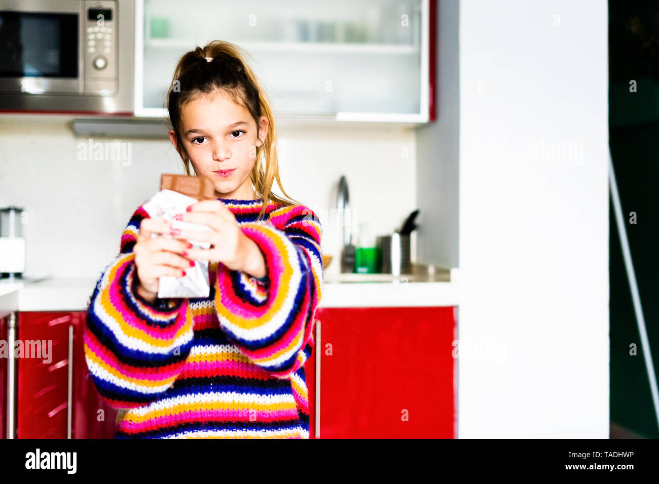 Portrait of girl in striped pullover in kitchen at home eating chocolate - Stock Image