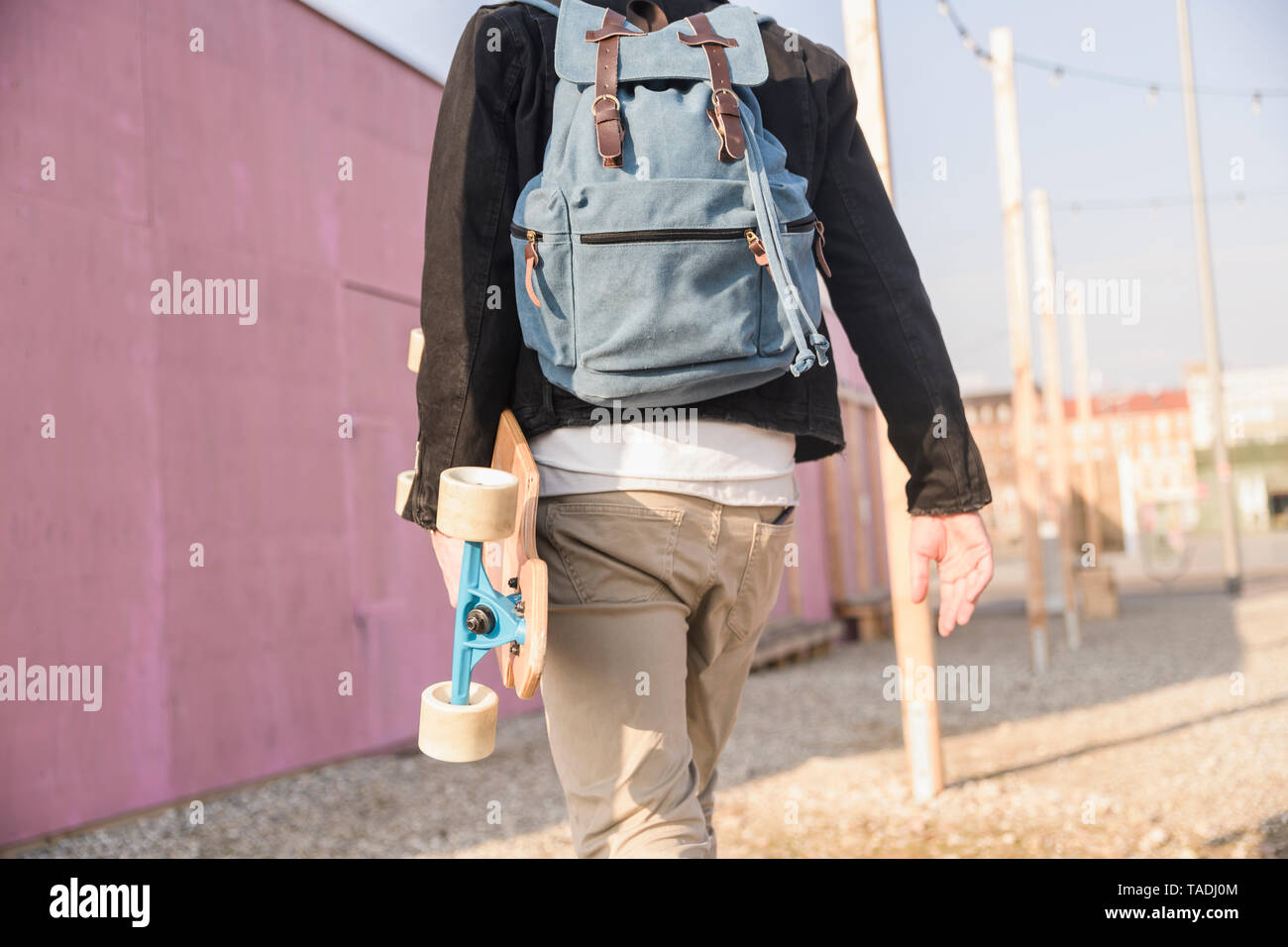 Rear view of young man with skatebaord and backpack on the move in the city - Stock Image