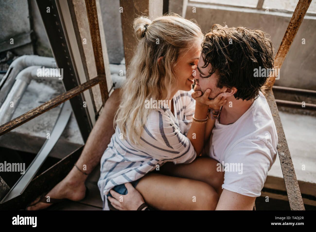 Young couple kissing in an old building - Stock Image