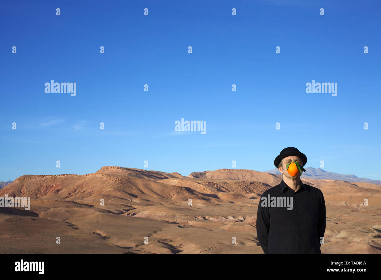 Morocco, Ounila Valley, man wearing a bowler hat with an orange in front of his face - Stock Image