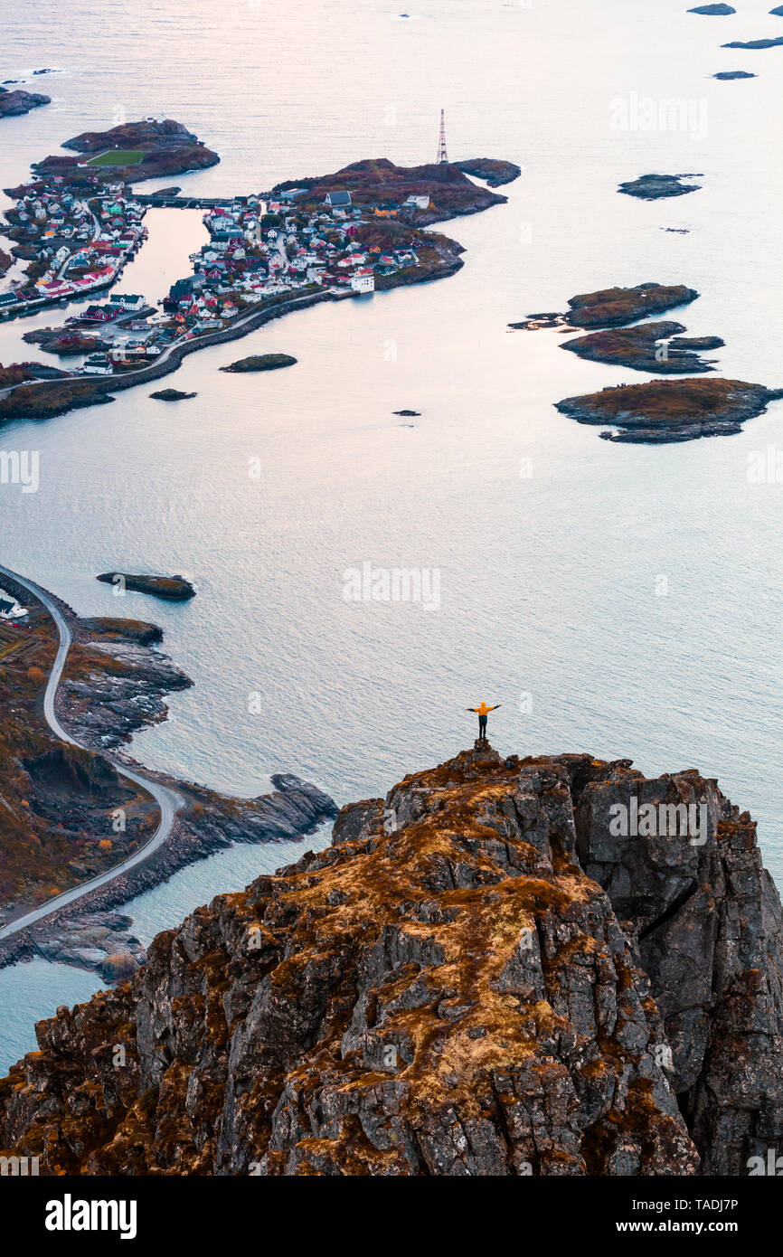 Norway, Lofoten Islands, Henningsvaer, man standing on viewing point with raising arms - Stock Image