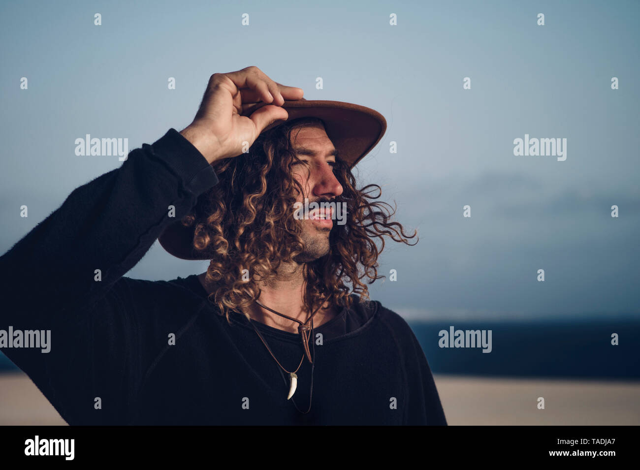 Young man with hat and mustache in the dunes - Stock Image