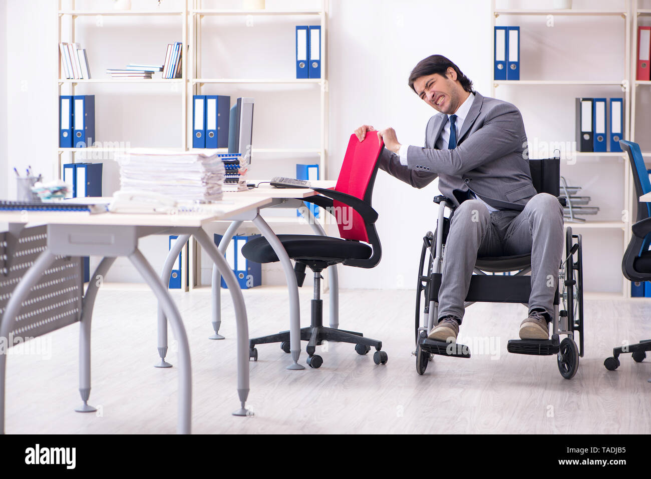 Young handsome employee in wheelchair working in the office - Stock Image
