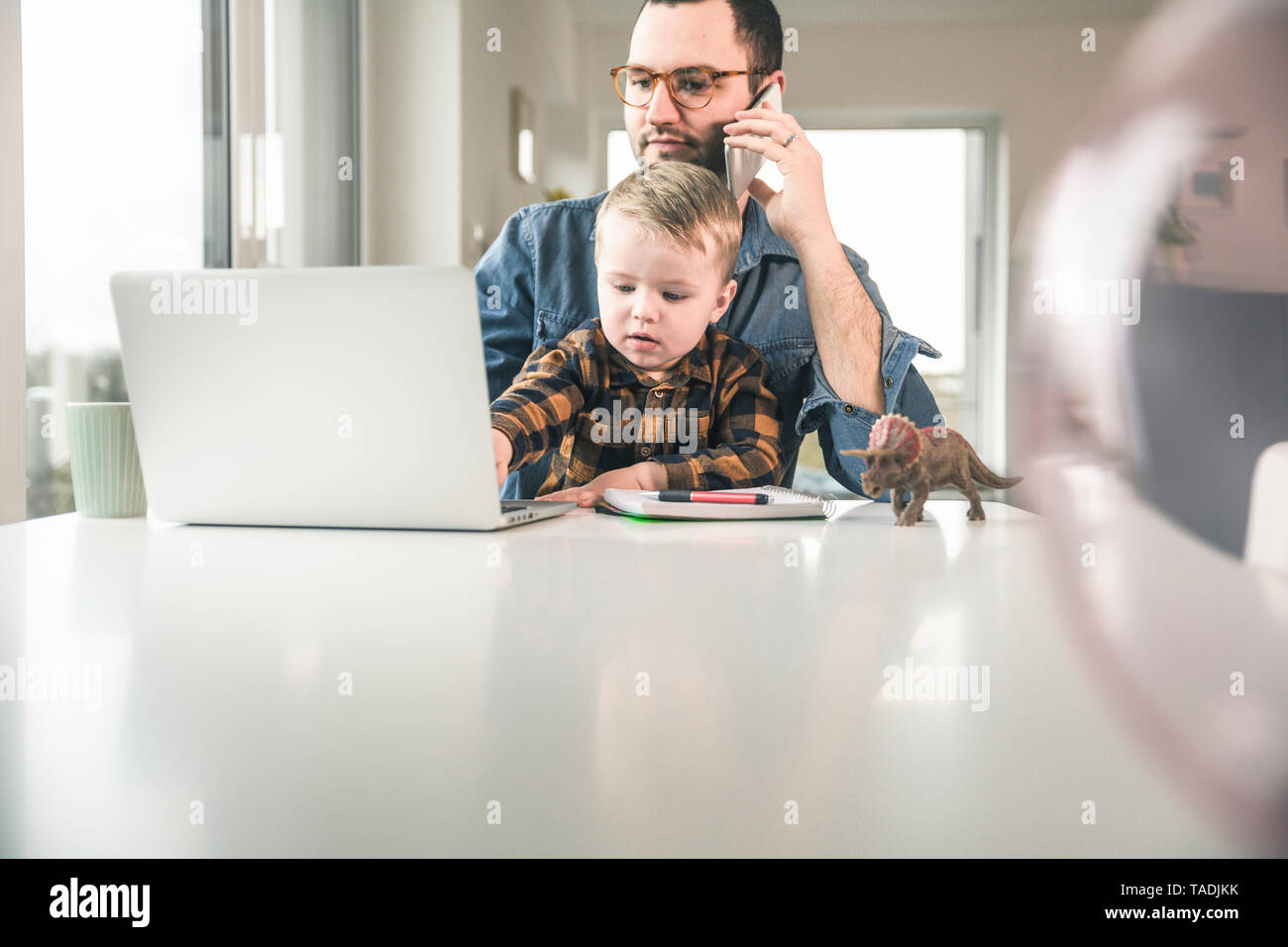 Father working at table in home office with son sitting on his lap - Stock Image