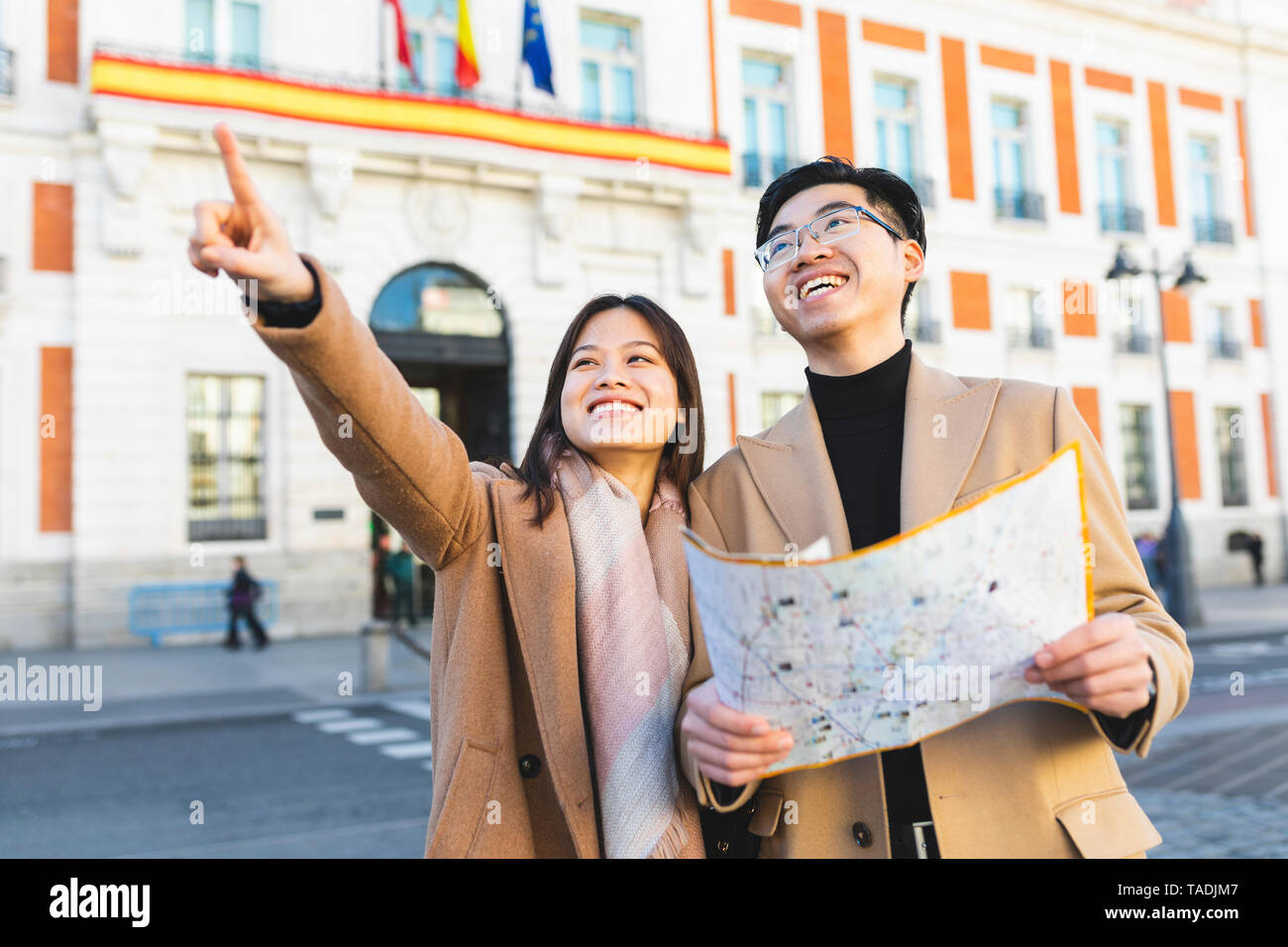 Spain, Madrid, happy young couple with map exploring the city - Stock Image