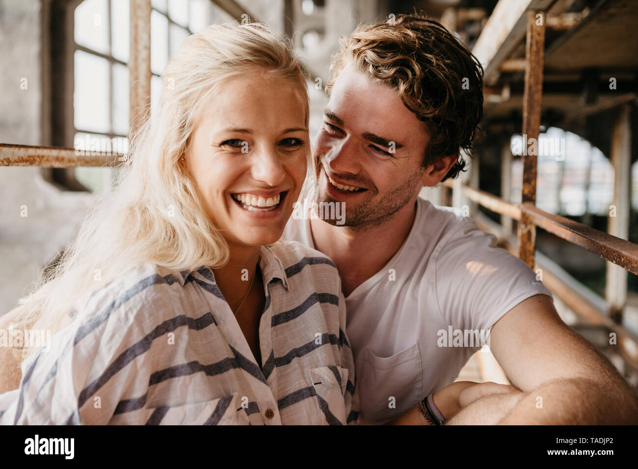 Portrait of happy young couple in an old building - Stock Image