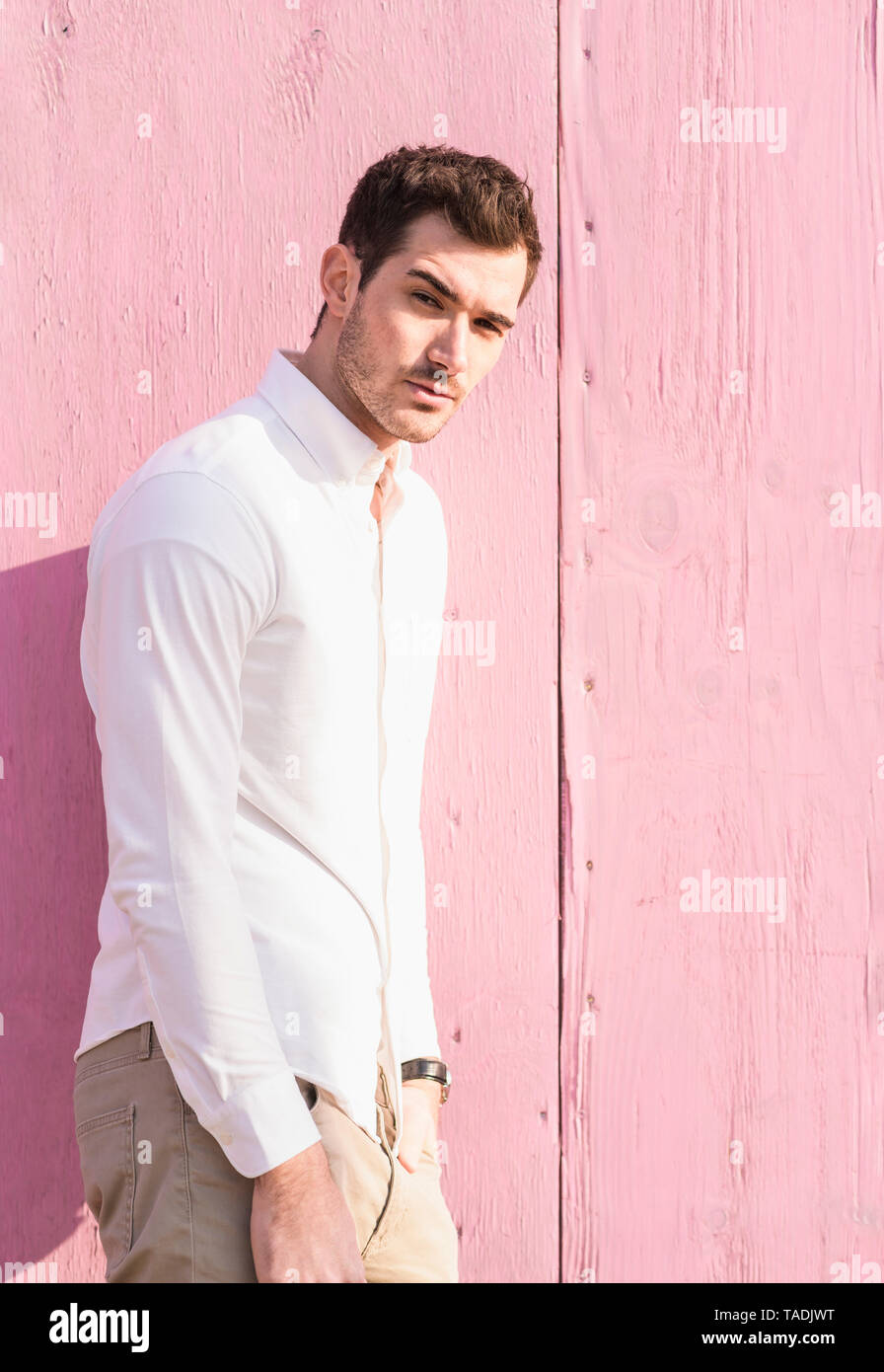 Portrait of young man standing in front of pink wall - Stock Image