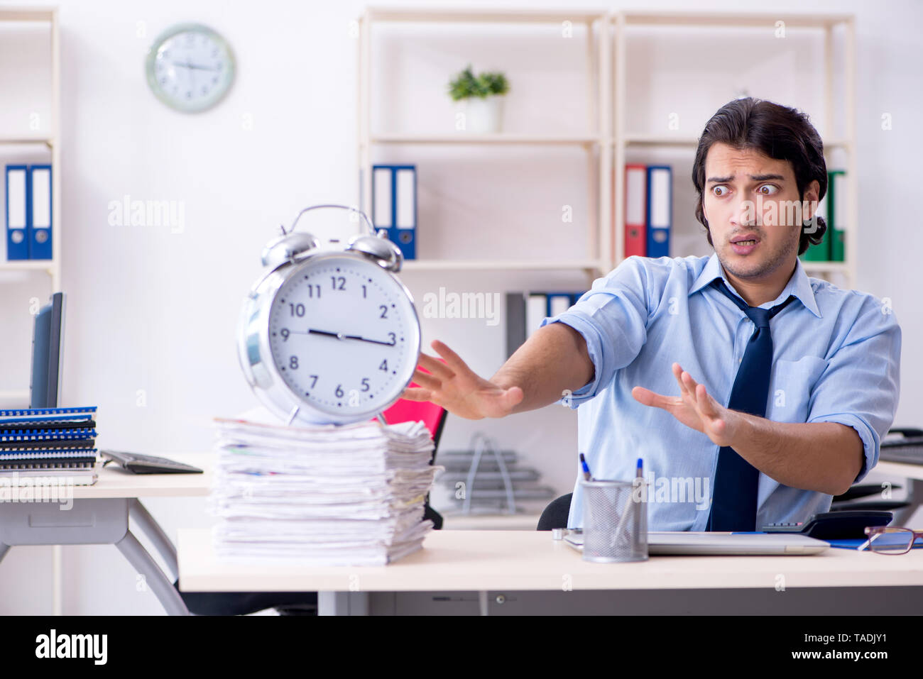 Young male businessman employee unhappy with excessive work - Stock Image