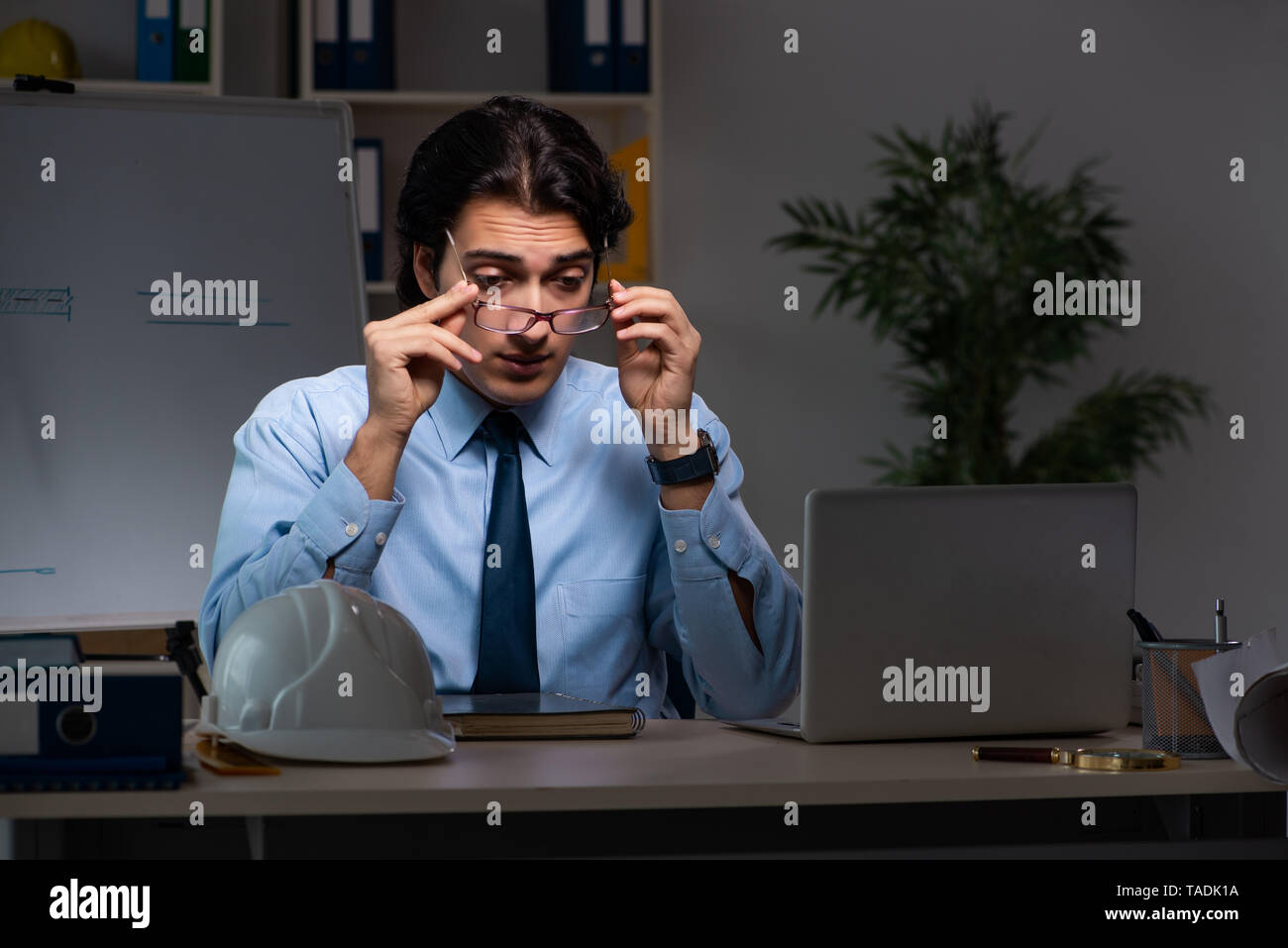 Young male architect working night at office - Stock Image