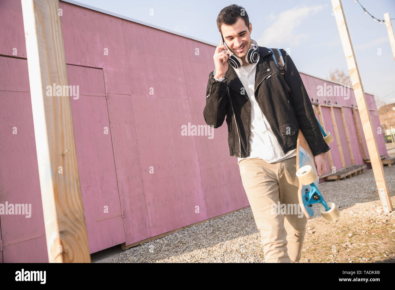 Young man with skatebaord and cell phone on the move - Stock Image