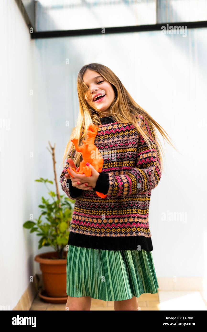 Portrait of happy girl playing with dinosaur toy at home Stock Photo