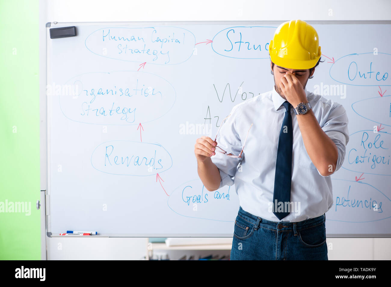 Young male architect in front of the whiteboard - Stock Image