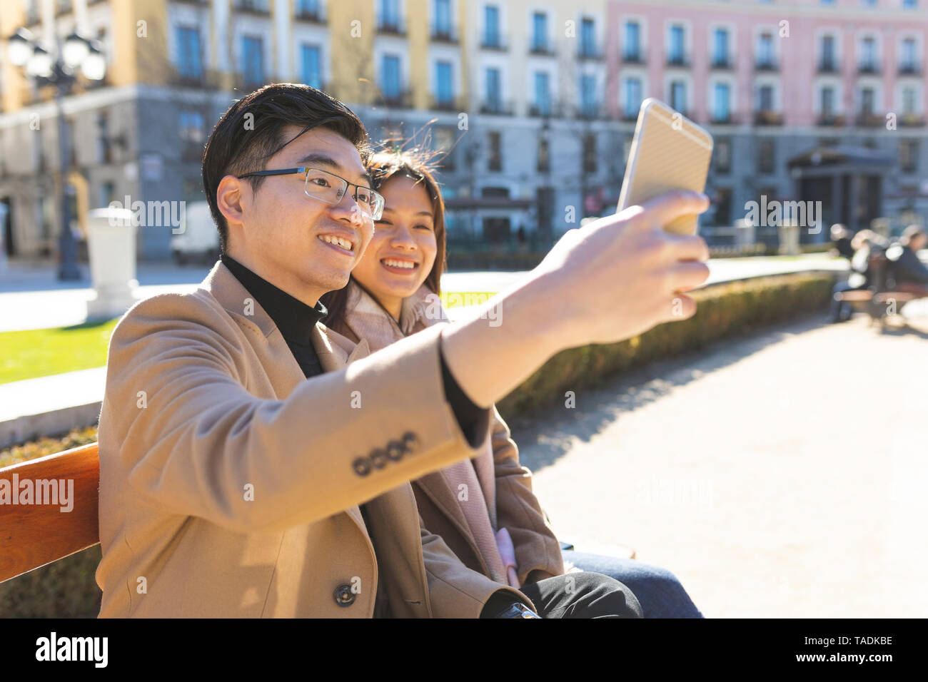 Spain, Madrid, young couple resting on a bench and taking a selfie in the city - Stock Image