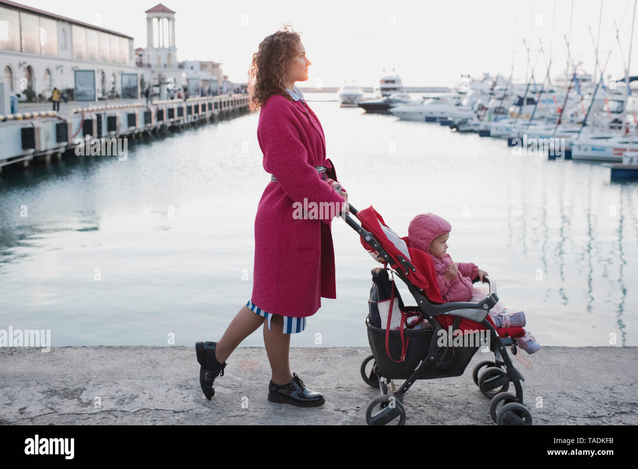 Mother pushing daughter in stroller at a marina - Stock Image